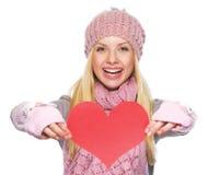 Muchacha sonriente en el sombrero del invierno que muestra la postal en forma de corazón Imagenes de archivo