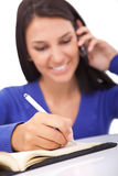 Muchacha sonriente en el teléfono que hace notas, Imagen de archivo libre de regalías