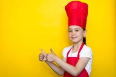 Muchacha sonriente en el traje y mostrar de un cocinero rojo el gesto del pulgar para arriba en un fondo amarillo con el espacio  imágenes de archivo libres de regalías