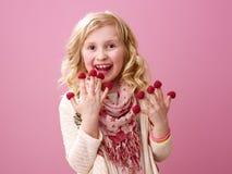 Muchacha sonriente en fondo rosado que come las frambuesas en los fingeres Fotos de archivo