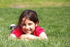 Muchacha sonriente en hierba Fotos de archivo
