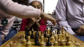 Muchacha sonriente en juego de ajedrez de observación del sombrero de santa almacen de video