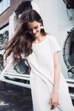 Muchacha sonriente en la calle en el vestido blanco con el pelo del vuelo Fotografía de archivo libre de regalías