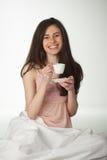 Muchacha sonriente en la cama con una taza de café Imagen de archivo libre de regalías