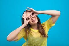 Muchacha sonriente en la camisa amarilla que hace caras Foto de archivo libre de regalías