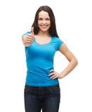 Muchacha sonriente en la camiseta azul que muestra los pulgares para arriba Fotografía de archivo libre de regalías
