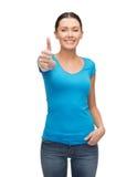 Muchacha sonriente en la camiseta azul que muestra los pulgares para arriba Foto de archivo libre de regalías