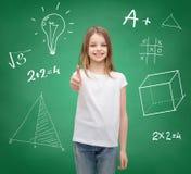 Muchacha sonriente en la camiseta blanca que muestra los pulgares para arriba Imagen de archivo libre de regalías
