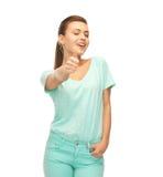 Muchacha sonriente en la camiseta del color que muestra los pulgares para arriba Fotos de archivo