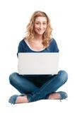 Muchacha sonriente en la computadora portátil Foto de archivo libre de regalías
