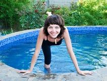 Muchacha sonriente en la piscina al aire libre foto de archivo libre de regalías