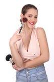 Muchacha sonriente en la presentación superior del rosa con los cosméticos Cierre para arriba Fondo blanco Foto de archivo