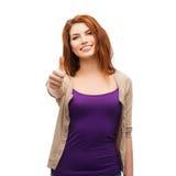 Muchacha sonriente en la ropa casual que muestra los pulgares para arriba Imagen de archivo