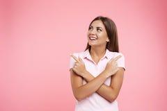 Muchacha sonriente en la ropa de deportes rosada que mira lejos con las manos a través Foto de archivo