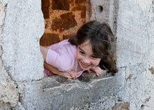 Muchacha sonriente en la ventana del castillo Imágenes de archivo libres de regalías