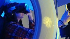 Muchacha sonriente en las auriculares de la realidad virtual que toman selfies en su teléfono Imagen de archivo libre de regalías