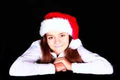 Muchacha sonriente en sombrero de la Navidad sobre obscuridad Fotografía de archivo libre de regalías