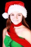Muchacha sonriente en sombrero de la Navidad sobre obscuridad Foto de archivo libre de regalías