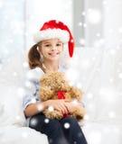 Muchacha sonriente en sombrero del ayudante de santa con el oso de peluche Imagen de archivo libre de regalías
