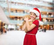 Muchacha sonriente en sombrero del ayudante de santa con el oso de peluche Imágenes de archivo libres de regalías