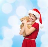 Muchacha sonriente en sombrero del ayudante de santa con el oso de peluche Fotografía de archivo