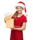 Muchacha sonriente en sombrero del ayudante de santa con la caja de regalo Fotografía de archivo