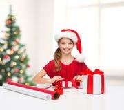 Muchacha sonriente en sombrero del ayudante de santa con la caja de regalo Fotos de archivo
