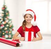Muchacha sonriente en sombrero del ayudante de santa con la caja de regalo Fotografía de archivo libre de regalías