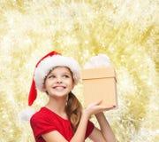 Muchacha sonriente en sombrero del ayudante de santa con la caja de regalo Foto de archivo libre de regalías