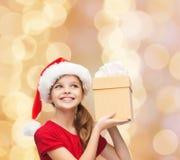 Muchacha sonriente en sombrero del ayudante de santa con la caja de regalo Foto de archivo