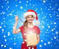 Muchacha sonriente en sombrero del ayudante de santa con la caja de regalo Fotos de archivo libres de regalías