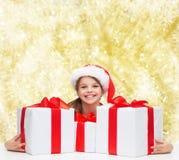 Muchacha sonriente en sombrero del ayudante de santa con las cajas de regalo Imagen de archivo libre de regalías