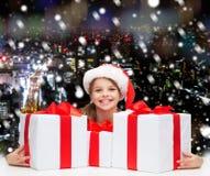 Muchacha sonriente en sombrero del ayudante de santa con las cajas de regalo Foto de archivo