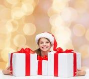 Muchacha sonriente en sombrero del ayudante de santa con las cajas de regalo Fotografía de archivo libre de regalías