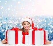 Muchacha sonriente en sombrero del ayudante de santa con las cajas de regalo Fotos de archivo