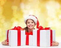 Muchacha sonriente en sombrero del ayudante de santa con las cajas de regalo Fotografía de archivo