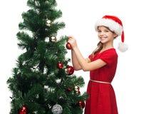 Muchacha sonriente en sombrero del ayudante de santa que adorna un árbol Fotografía de archivo