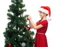 Muchacha sonriente en sombrero del ayudante de santa que adorna un árbol Fotografía de archivo libre de regalías