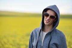 Muchacha sonriente en sudadera con capucha y gafas de sol en el aire libre Fotografía de archivo