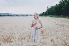 Muchacha sonriente en un campo de trigo Foto de archivo
