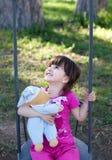 Muchacha sonriente en un oscilación Fotos de archivo libres de regalías