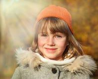 Muchacha sonriente en un parque del otoño Foto de archivo