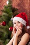 Muchacha sonriente en un sombrero de la Navidad Fotos de archivo