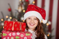 Muchacha sonriente en un sombrero de Papá Noel con sus regalos Fotos de archivo