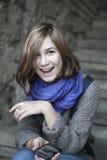 Muchacha sonriente en una bufanda azul que se sienta en las escaleras de piedra Foto de archivo libre de regalías