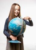 Muchacha sonriente en uniforme escolar que señala en el globo de la tierra Fotografía de archivo libre de regalías