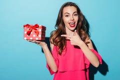 Muchacha sonriente en vestido que señala el finger en una caja de regalo Fotografía de archivo