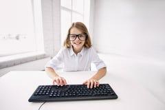 Muchacha sonriente en vidrios con el teclado en la escuela Imagen de archivo libre de regalías