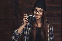 Muchacha sonriente en vidrios con la cámara del vintage Fotografía de archivo libre de regalías