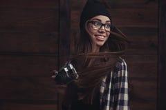 Muchacha sonriente en vidrios con la cámara del vintage Imágenes de archivo libres de regalías